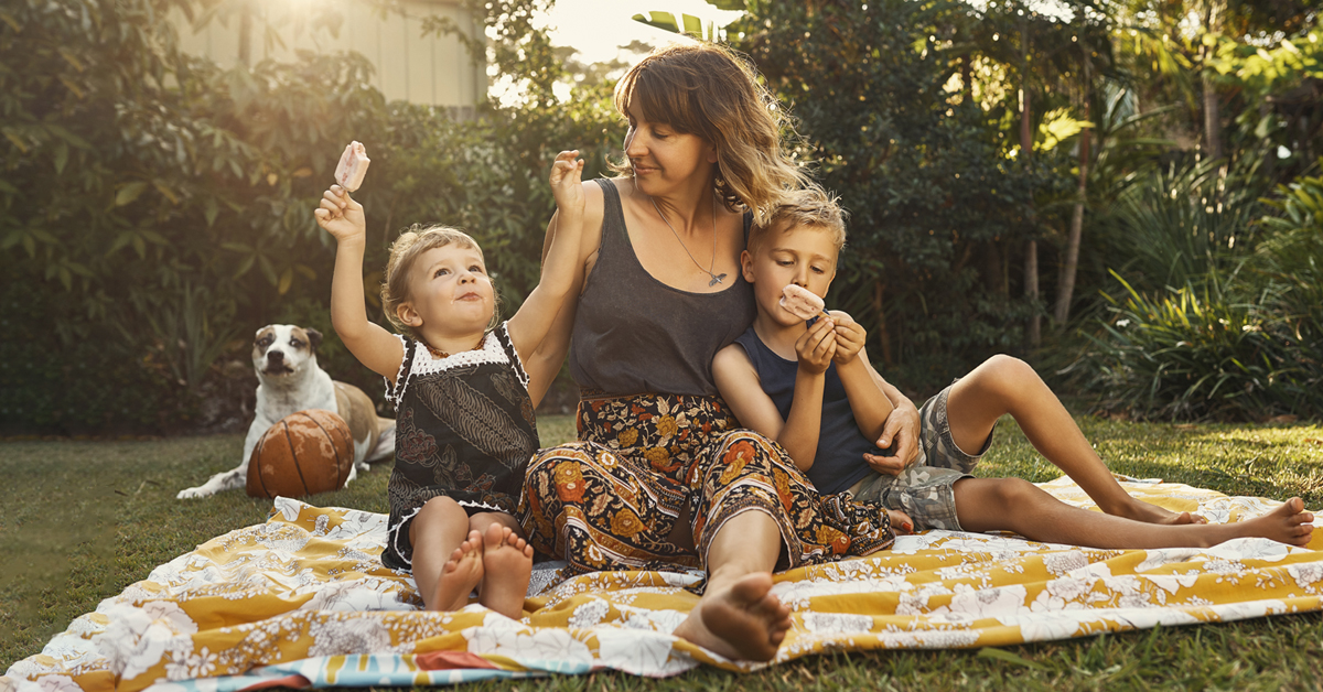 Mother and her children eating ice cream on picnic blanket