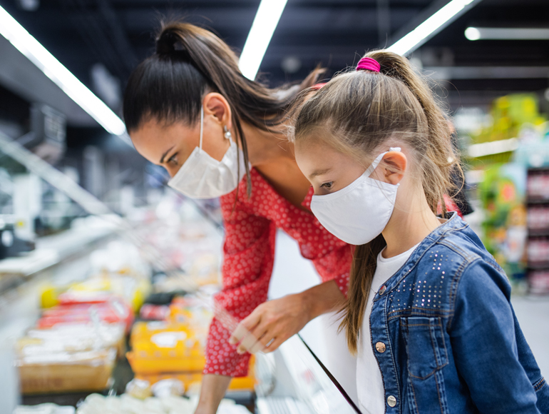 Mother and daughter shopping wearing masks